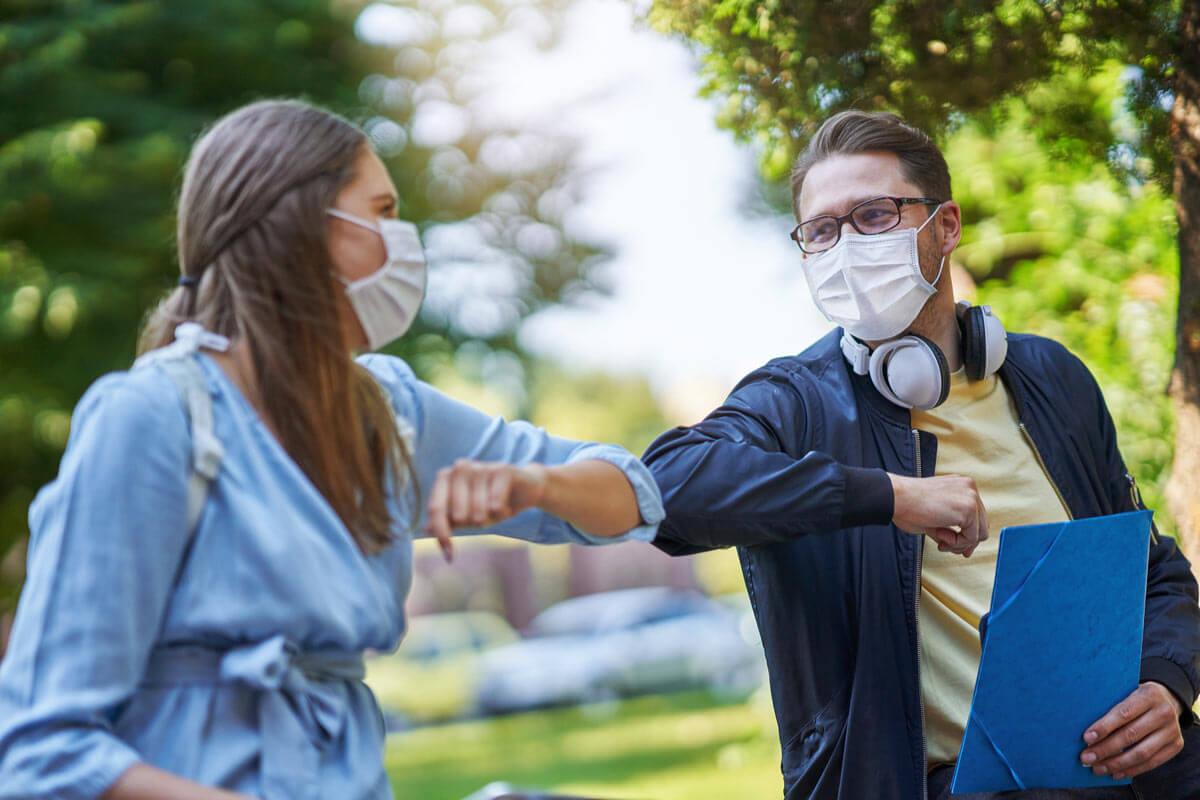 zwei Studenten in Masken begrüßen sich in sozialer Distanz mit Ellenborgen
